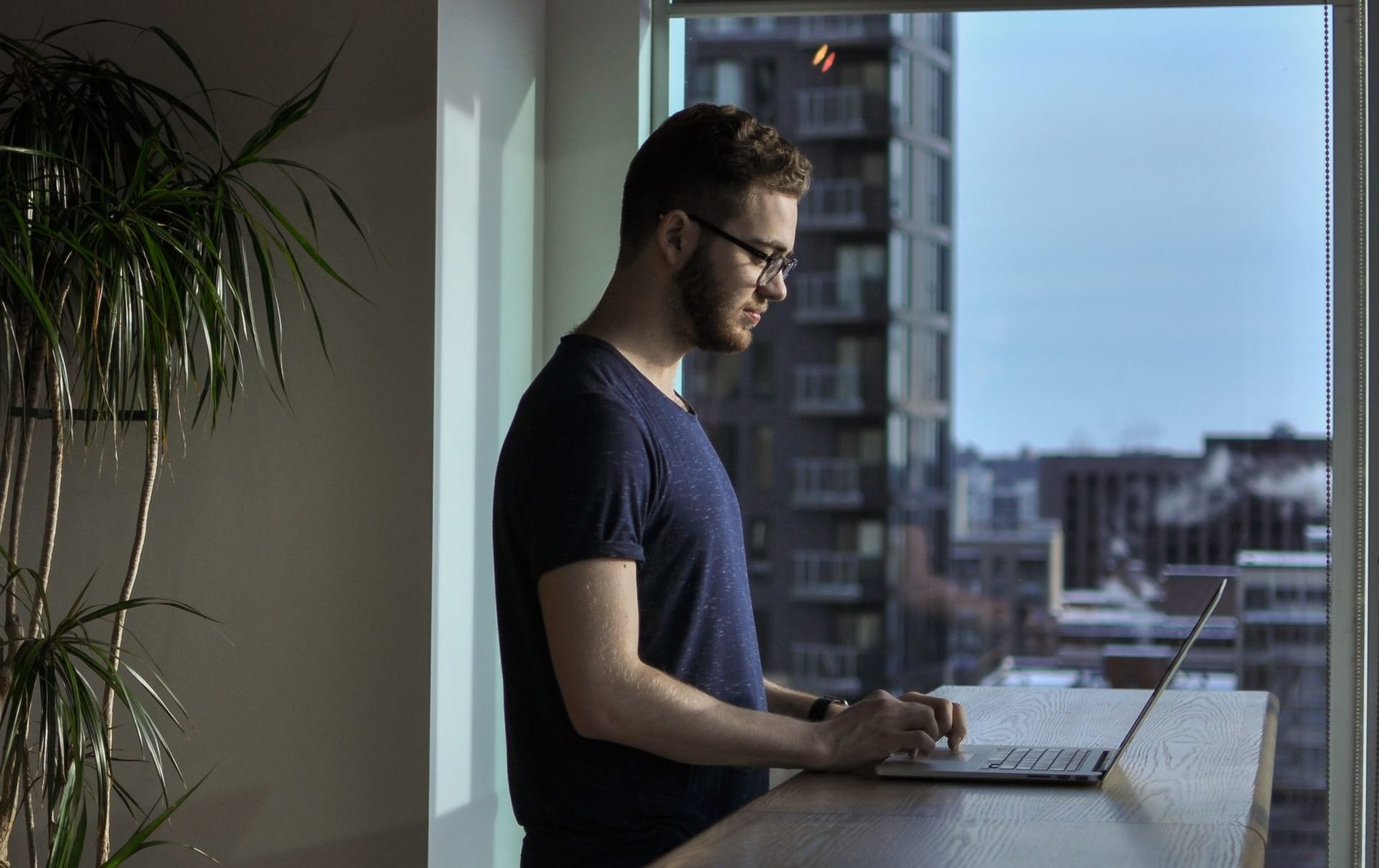 man working on laptop in front of window looking out into the city