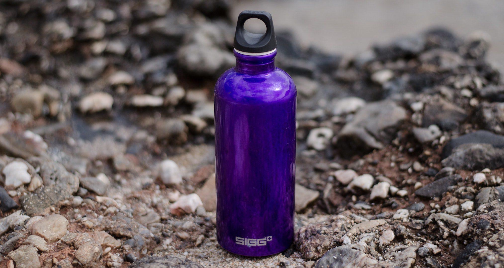 purple water bottle sitting on rocks