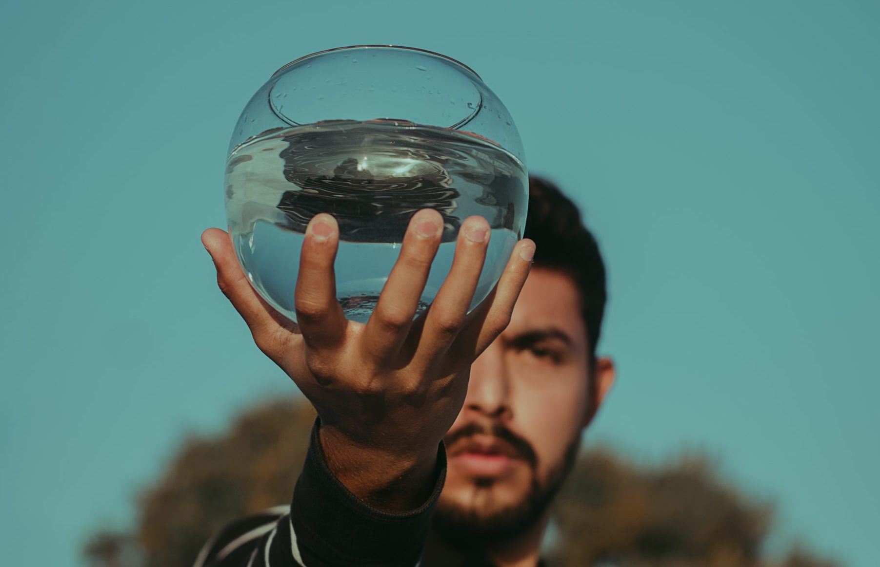 man holding a clear fish bowl of water in out-stretched hand
