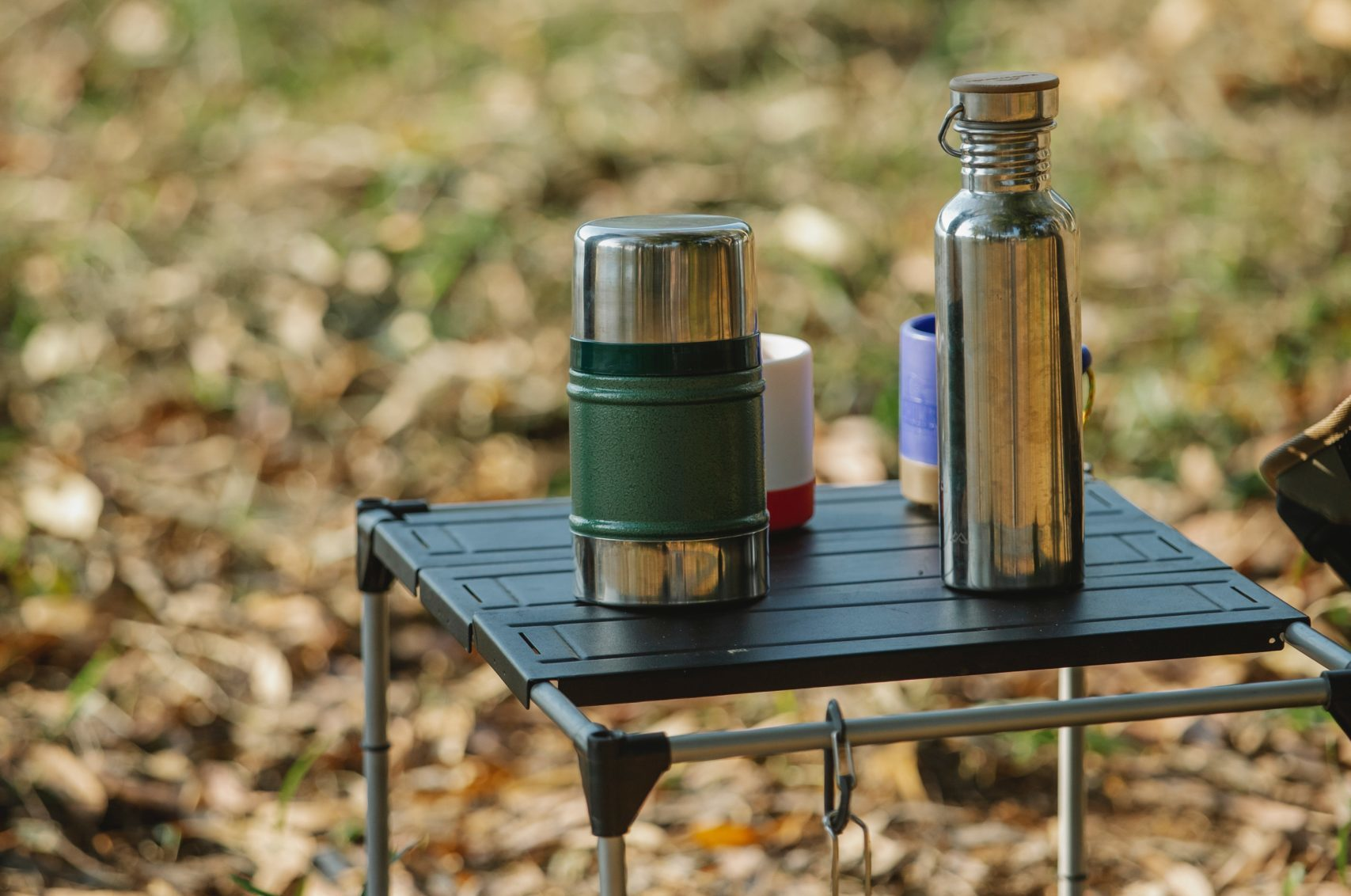 stainless steel water bottles outside on a small table