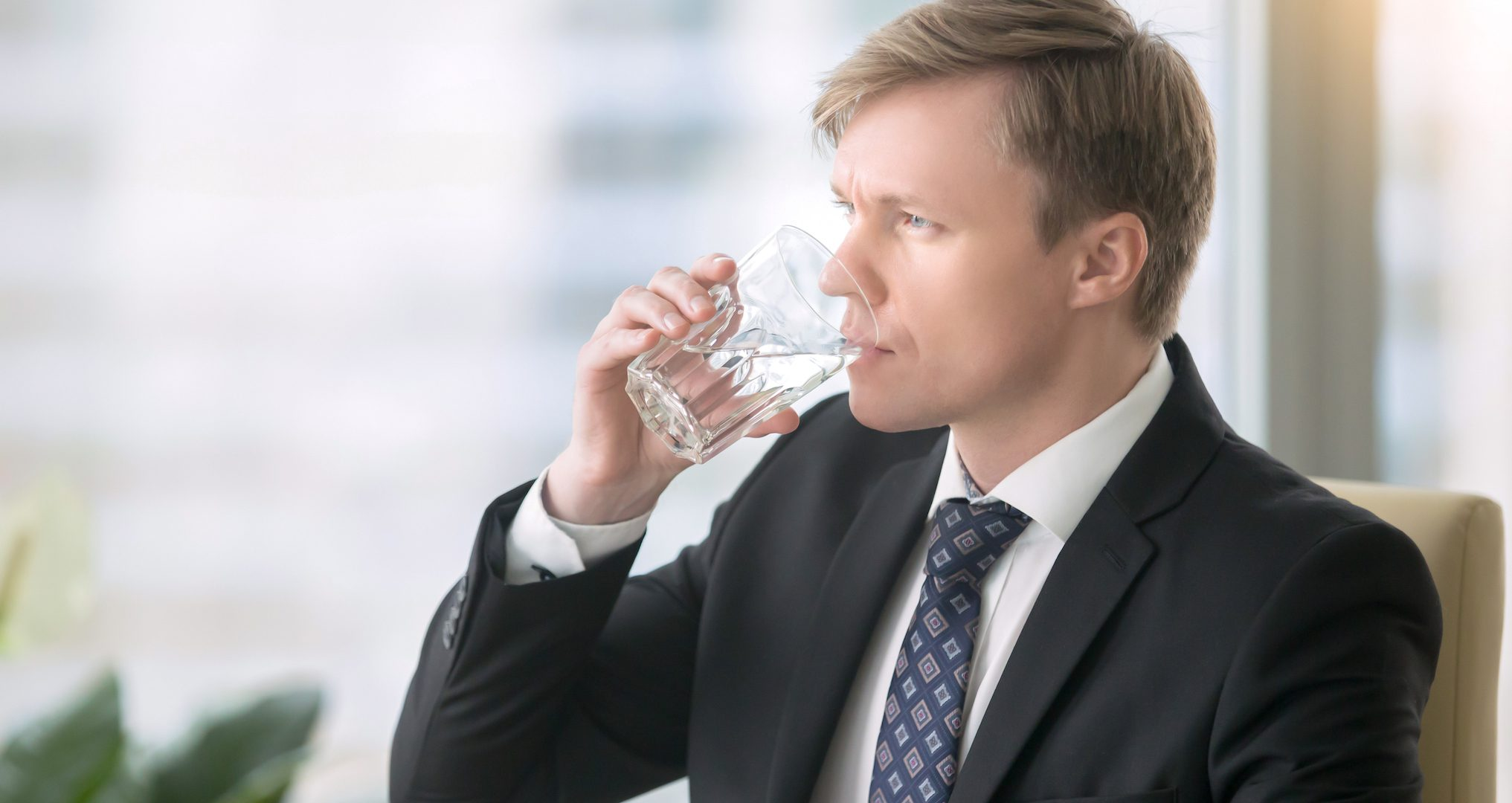 man in a business suit drinking a glass of water
