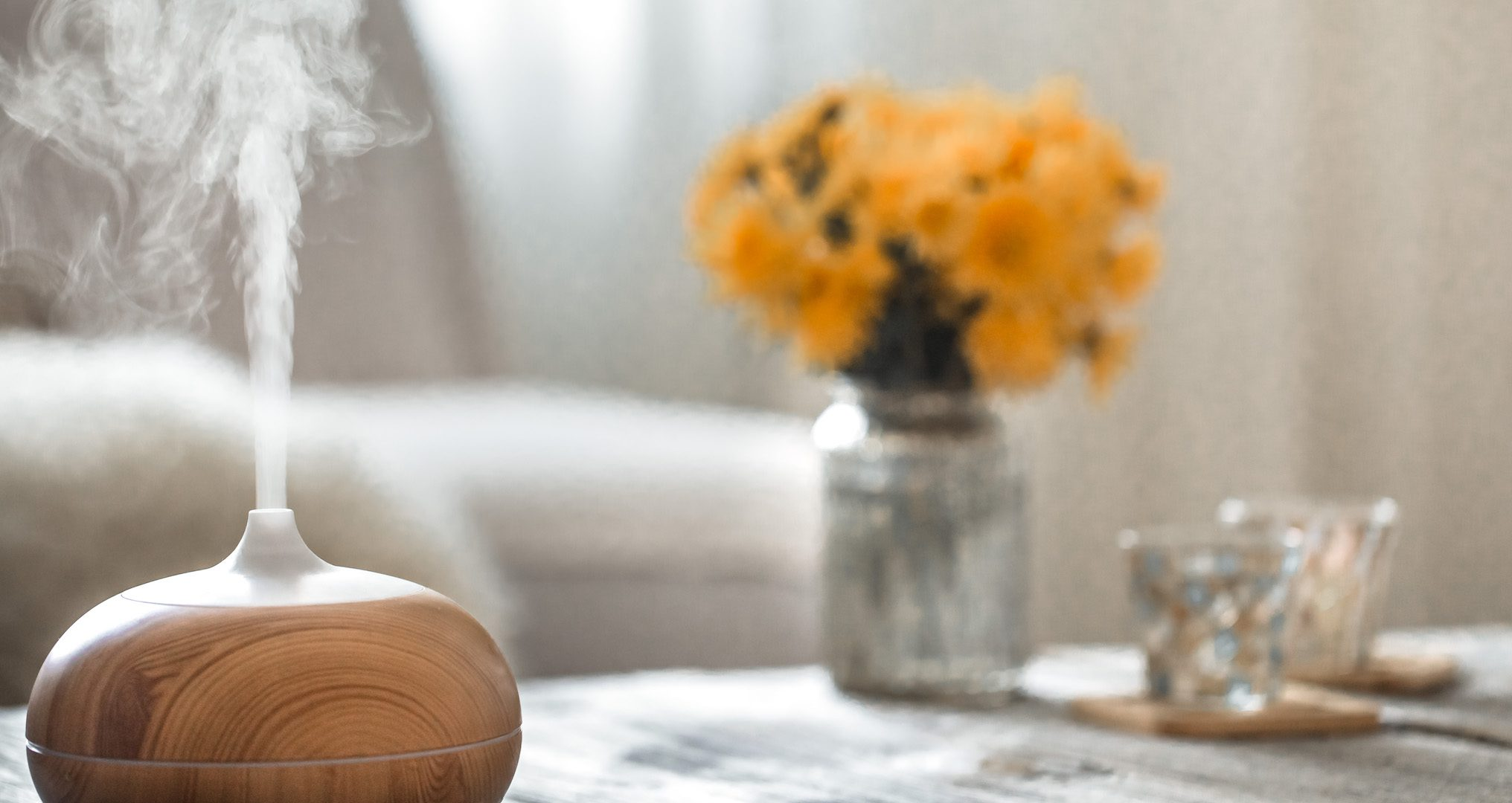 brown wooden humidifier with steam coming out on a table with flowers and candles