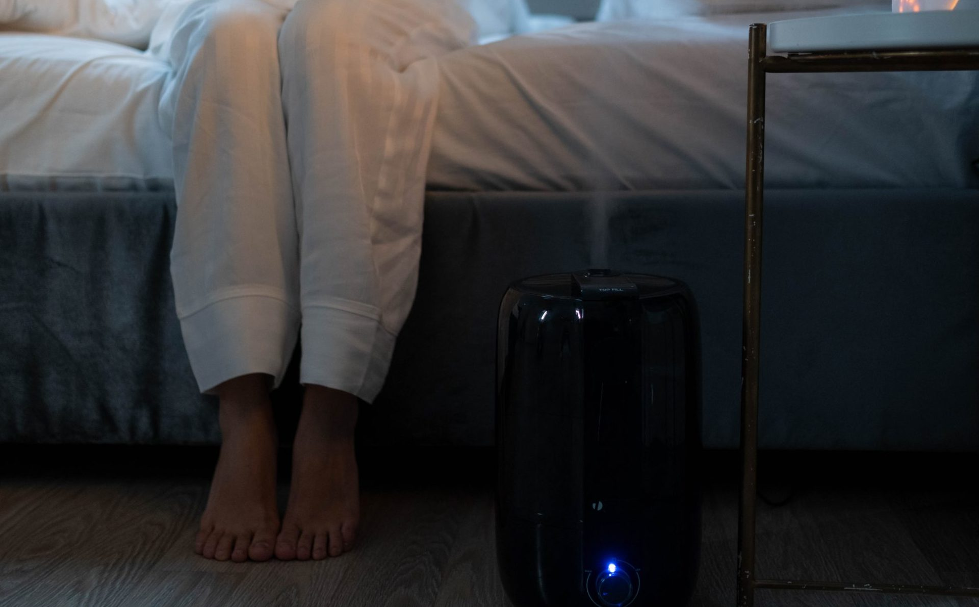 humidifier next to woman sitting on bed