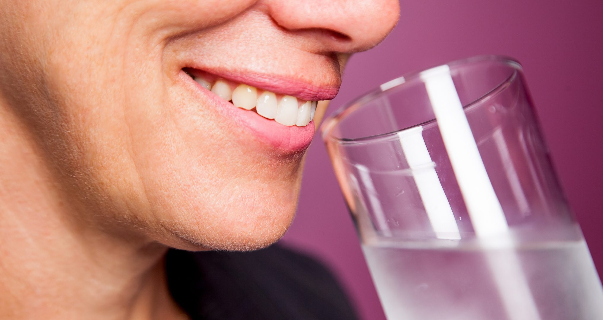 woman smiling and drinking a glass of water