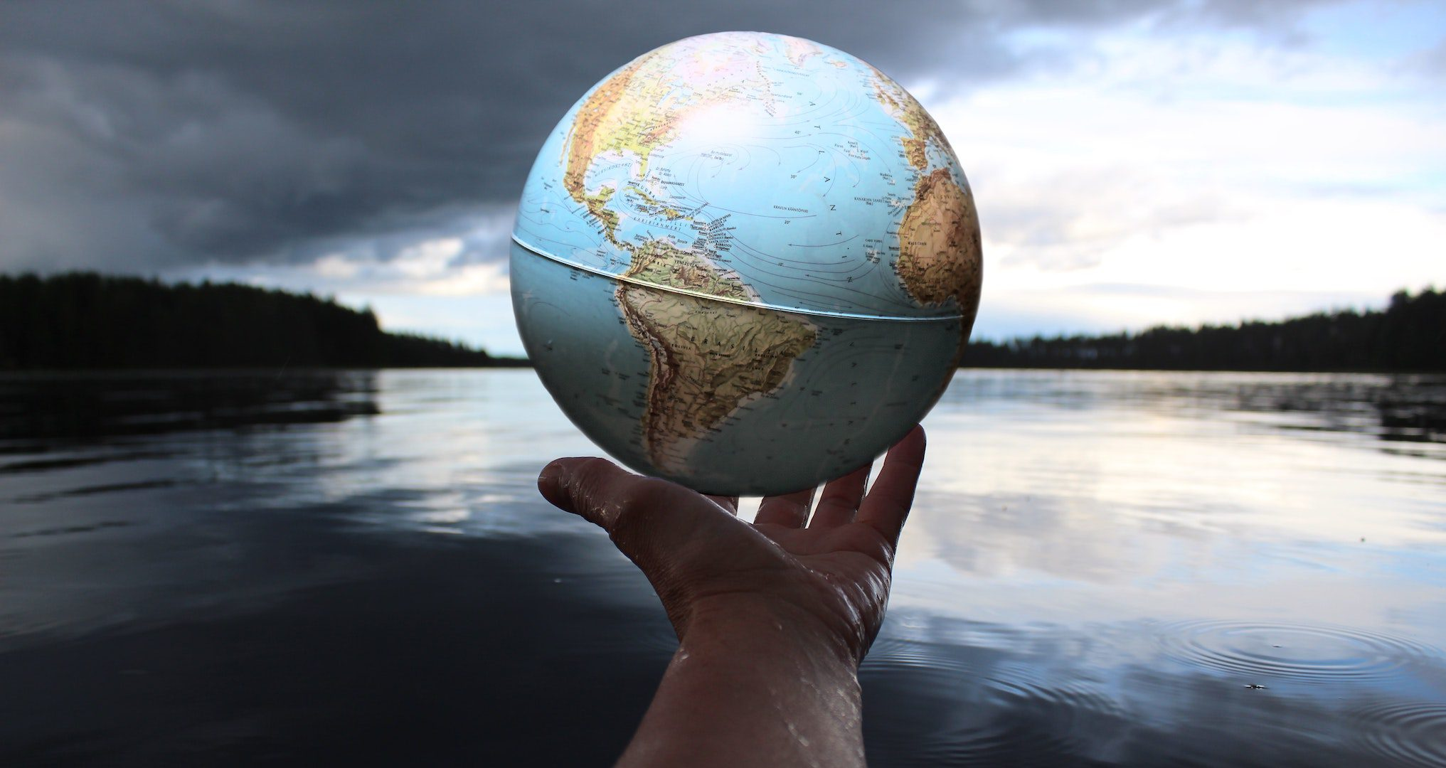 person holding a globe in the palm of their hand with a lake in the background
