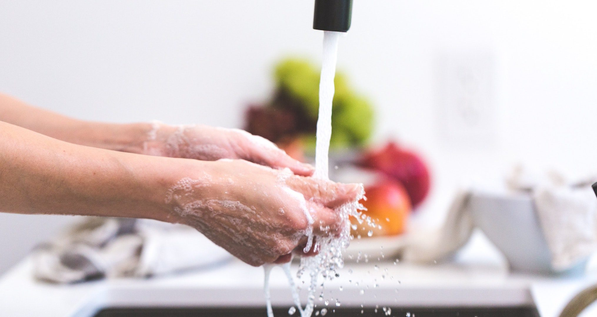 woman washing her hands at the kitchen sink with food in the background